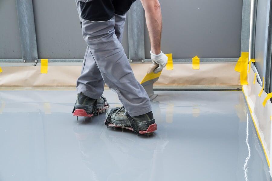 worker installing epoxy in basement